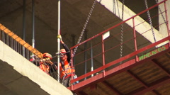 Workers install a jack between the floor slabs at the construction site. Stock Footage
