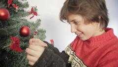 Boy putting ornament on Christmas tree - stock footage