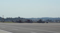 Military Helicopters wait on tarmac Stock Footage