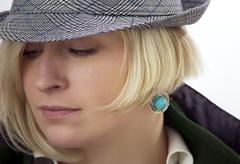 Woman's face with a cyan earring Stock Photos