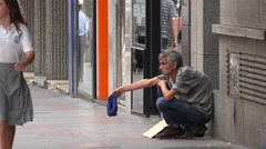 Beggar on sidewalk in Alicante Stock Footage