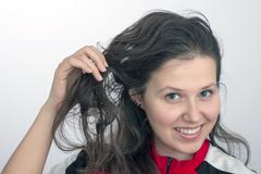 smiling girl's face and hand tousling hair - stock photo