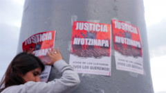 Woman sticking a banner in a march protest for the disappeared in Ayotzinapa. Stock Footage