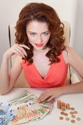 Beautiful business woman in  pink dress on  table are banknotes of  Euro and USD Stock Photos