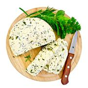 cheese homemade with knife and herbs on round board - stock photo
