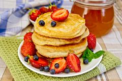 flapjacks with strawberries and blueberries with napkin - stock photo