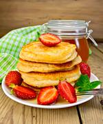 flapjacks with strawberries and honey on board - stock photo