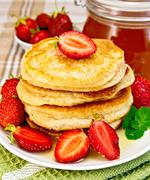 flapjacks with strawberries and honey on tablecloth - stock photo