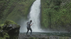 Man jumping next to waterfall Stock Footage