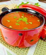 soup tomato in red ware on napkin - stock photo