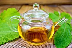 Tea in teapot with sage on bamboo napkin Stock Photos