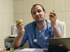 Happy doctor giving advice and recommending to eat apple and pepper Stock Footage