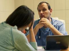 Male doctor telling bad news to worried female patient in hospital NTSC Stock Footage
