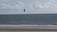 Solitary kitesurfer riding the North Sea waves at the Dutch coast - wide shot. Stock Footage