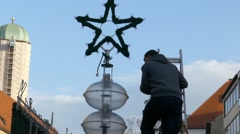 4K FHD Worker decorating street light with Christmas star Stock Footage