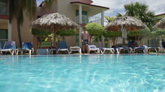 Teenager floats in pool Stock Footage