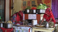 Rajasthani women preparing chapatis on fire at an outdoor cafe. Pushkar, India Stock Footage