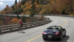 Cyclists ride over linn cove viaduct, blue ridge parkway in the fall, nc Stock Footage