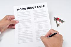 a young man signing a home insurance policy - stock photo