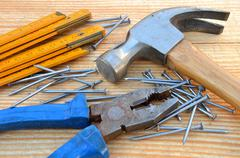 claw hammer, carpenter meter, pliers and nails - stock photo