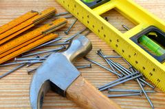 claw hammer, carpenter meter, water-level and nails - stock photo