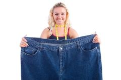 Stock Photo of Woman in dieting concept with big jeans