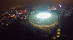 Aerial of large illuminated stadium at night, city landmark - stock footage