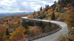 Car drives over linn cove viaduct, blue ridge parkway in the fall, nc Stock Footage