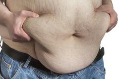 overweight man ipinching belly fat - stock photo