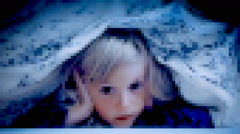 Little girl under bed sheets scared pixelated Stock Footage