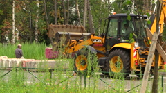 The tractor JCB on a construction site moves concrete blocks. Stock Footage