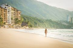 Mexico, Puerto Vallarta, woman wearing bikini walking at the Punta Negra beach - stock photo