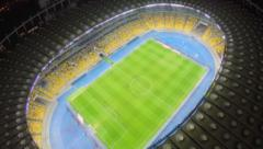 Footballers playing match on field, stadium, fan-zone, aerial, click for HD Stock Footage