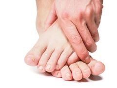 Male hand holding onto feet Stock Photos