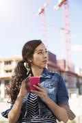 Germany, Berlin, portrait of young female tourist orientating with her - stock photo