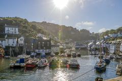 UK, Cornwall, Polperro, fishing boats in harbor in back light Stock Photos