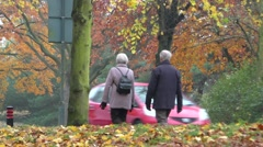 Elderly couple walking in park at autumn with cars passing Stock Footage