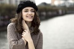 Stock Photo of Portrait of happy young woman wearing beret and knitted dress