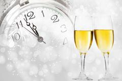 champagne against holiday lights and clock close to midnight - stock photo