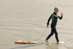 France, Brittany, Finistere, Plage de Treguer, boy with bodyboard Stock Photos