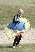 France, Brittany, Finistere, Plage de Treguer, boy with bodyboard pretending to Stock Photos