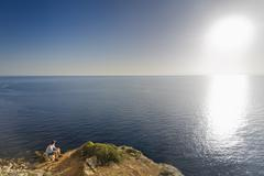Spain, Balearic Islands, Majorca, one teenage boy sitting on a rock at the cliff - stock photo