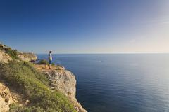 Spain, Balearic Islands, Majorca, one teenage boy standing on a rock at the Stock Photos