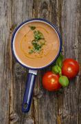 Saucepan of tomato sauce, tomatoes and basil leaves on wood - stock photo