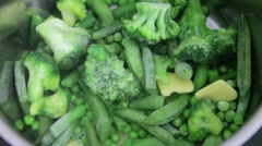 Cooking frozen green vegetables like peas, broccoli and beans Stock Footage