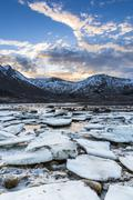 ice and rocks in a sundown at the coastline of gimsøy, Lofoten, Norway - stock photo