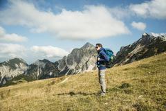 Austria, Tyrol, Tannheimer Tal, hiker with backpack on alpine meadow - stock photo