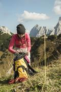 Austria, Tyrol, Tannheimer Tal, female hiker with backpack on alpine meadow - stock photo