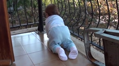 Baby on the balcony secured with metal net - stock footage