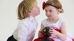 Little boy sniffs flower in hair of girl with ball-shaped lamp Stock Footage